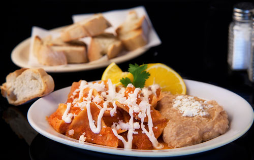 Red Chilaquiles with refried beans, bread and orange